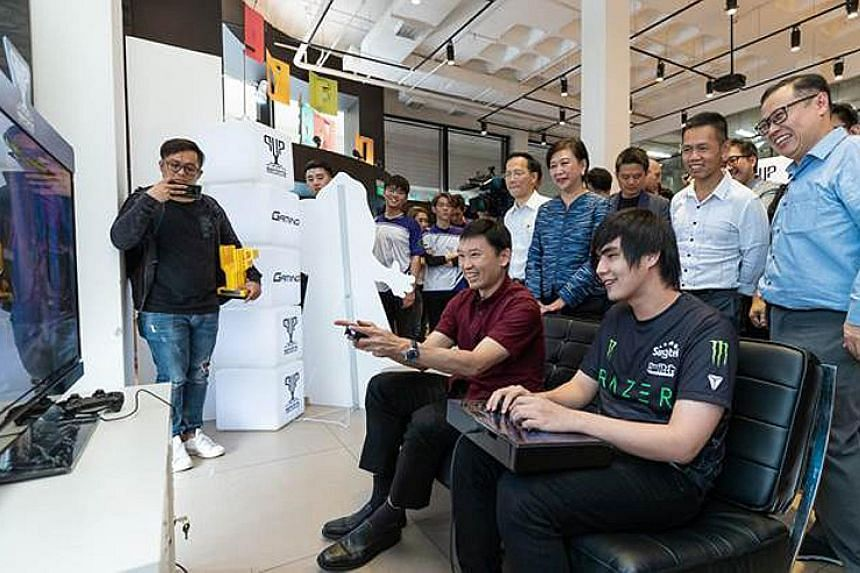 Senior Minister of State for Education Chee Hong Tat (in red shirt) taking on professional gamer Ho Kun Xian in the Street Fighter game at the launch of Singtel's e-sports community initiative on Wednesday.