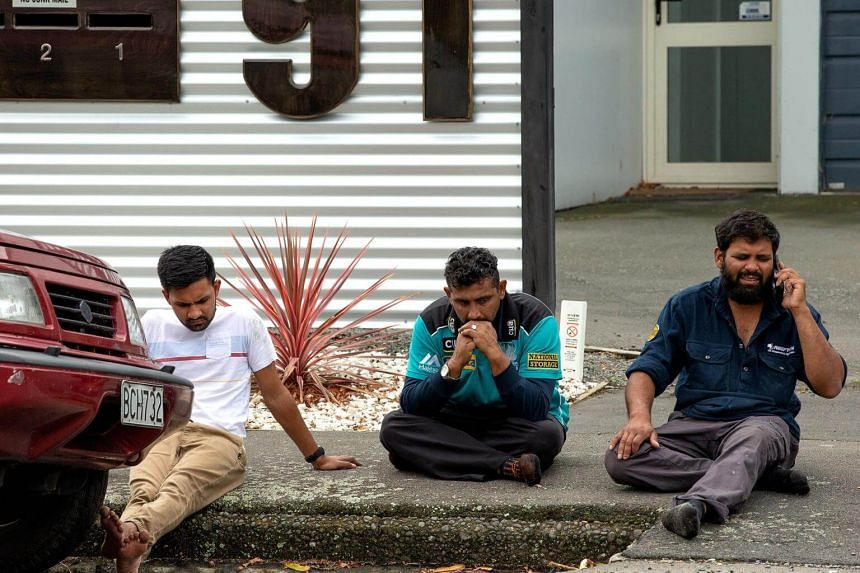 Grieving members of the public sit on a curb following a shooting at the Al Noor mosque in Christchurch, New Zealand, on March 15, 2019.