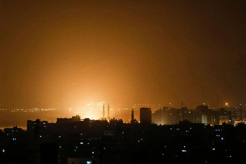 The sky above buildings on the Gaza Strip glows orange during an Israeli air strike in Gaza city, on March 15, 2019.