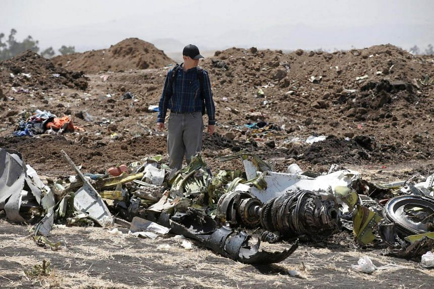American civil aviation and Boeing investigators search through the debris at the scene of the Ethiopian Airlines Flight ET 302 plane crash, on March 12, 2019.