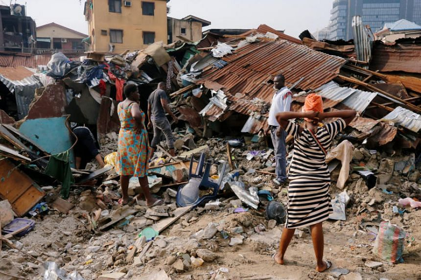 A woman searches for belongings at the site of a collapsed building in Nigeria's commercial capital of Lagos, Nigeria, on March 14, 2019.