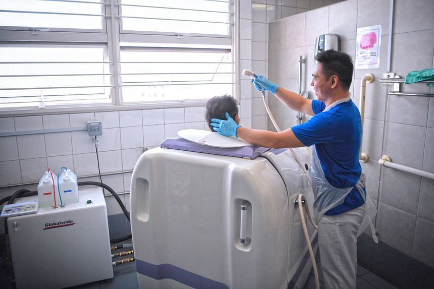 Right: Ren Ci Community Hospital nurse Maroger Paningbatan, 28, pushing a patient into the Viami RS-05 shower machine. The patient is seated on a specially designed commode chair. Below: While the machine washes the patient's body, the nurse can wash