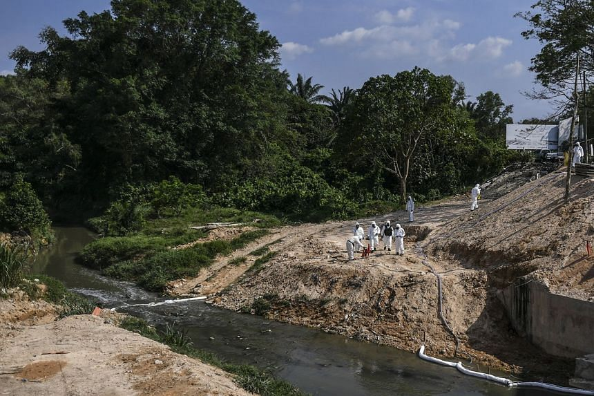Emergency personnel wearing protective suits clean up the Sungai Kim Kim river in Pasir Gudang, Johor, on March 14, 2019.