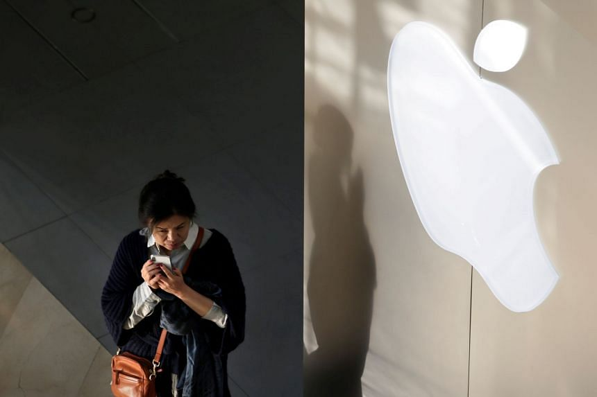 A woman holds her phone near an Apple company logo in Beijing, China.