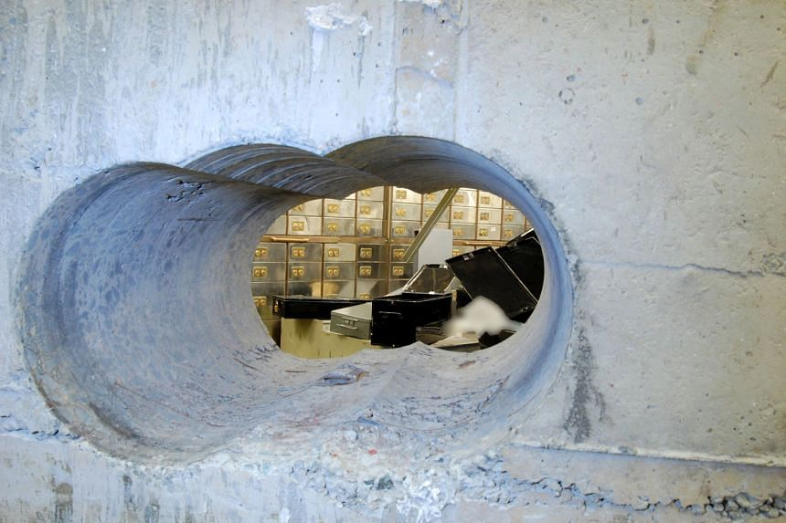 The gang used a diamond-tipped drill to bore through the concrete wall of a vault (above) over a long holiday weekend.