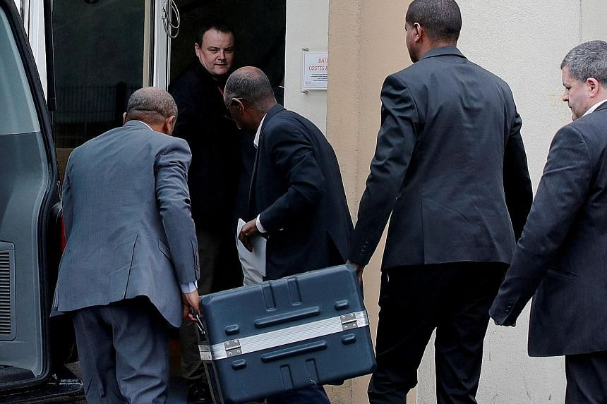 Men unloading a case containing black boxes from Ethiopian Airlines' crashed Boeing 737 Max at the Bureau of Enquiry and Analysis for Civil Aviation Safety in France on Thursday. Boeing is under scrutiny for the crash last weekend and has halted ship