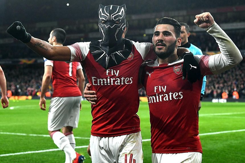 Arsenal's Pierre-Emerick Aubameyang (in mask) celebrating with Sead Kolasinac during the 3-0 Europa League last-16, second-leg win over Rennes on Thursday.