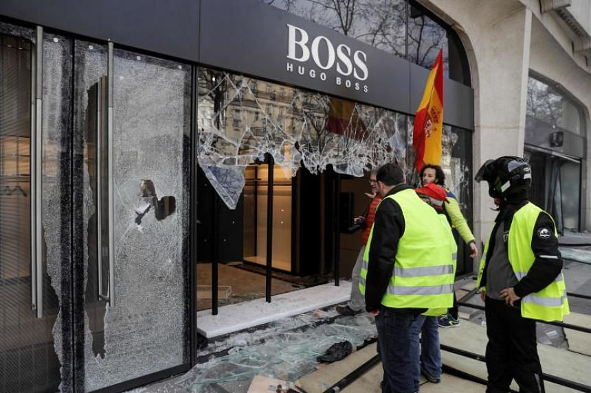 Protesters look at the destroyed window of a Hugo Boss store during clashes with riot police forces on the Champs-Elysees in Paris on March 16, 2019.