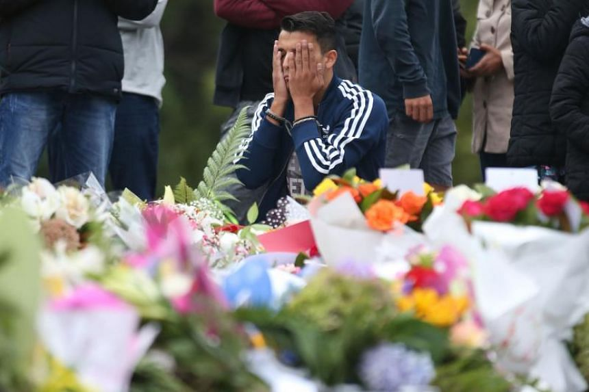 People pay their respects in front of floral tributes for victims of the March 15 mosque attacks, in Christchurch on March 16, 2019.