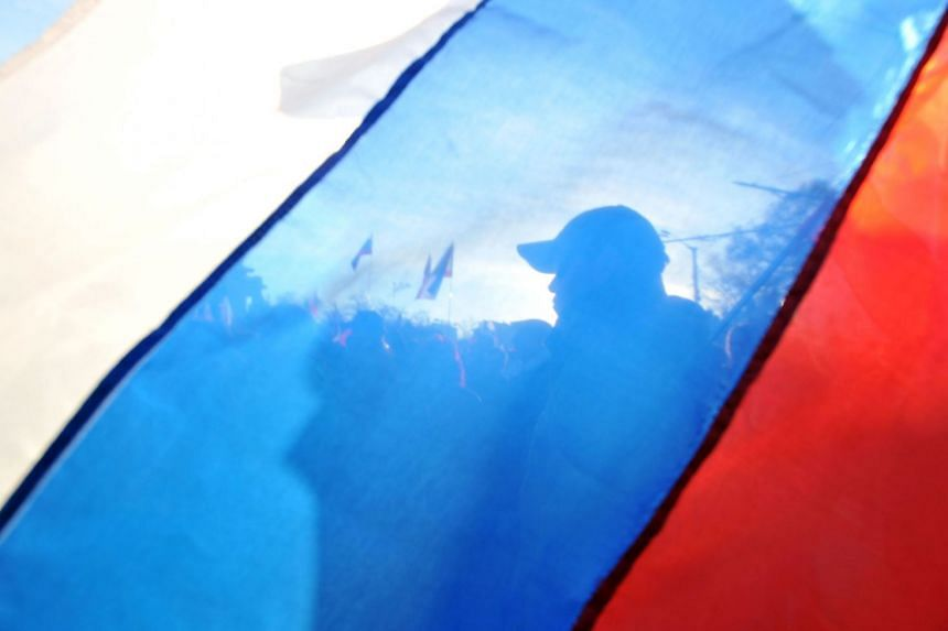 Pro-Russian activists stand behind a Russian flag during a rally in the Crimean city of Yevpatoria.