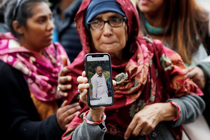 A woman holds up a photo of her husband who she says is missing after the mosque attacks, outside a community centre near Al Noor mosque in Christchurch, New Zealand, on March 16, 2019.