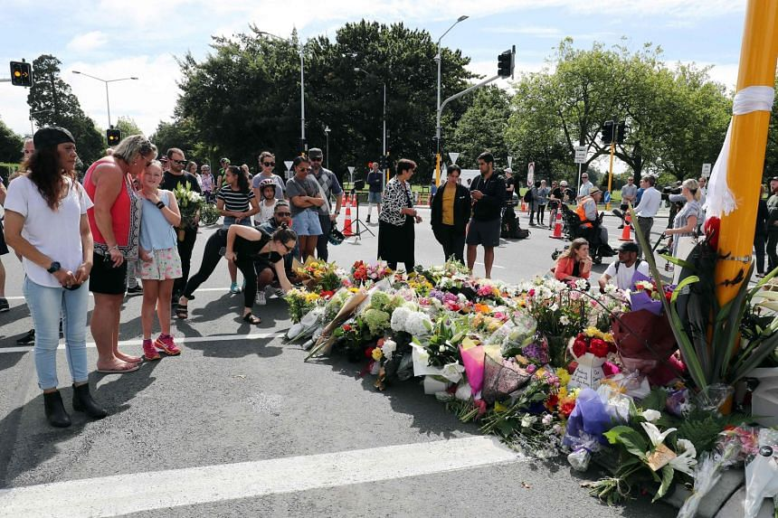 Residents pay their respects by placing flowers for the victims of the mosques attacks in Christchurch, on March 16, 2019.