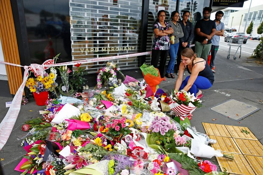 People place flowers at a memorial as a tribute to victims of the shootings, near Linwood Mosque in Christchurch, on March 16, 2019.