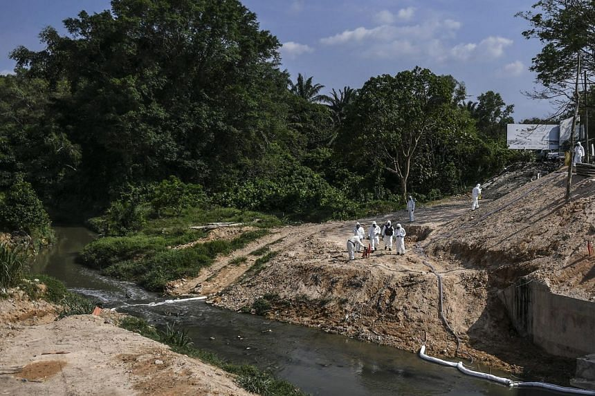 Emergency personnel in protective suits cleaning up the Sungai Kim Kim river in Pasir Gudang, on March 14, 2019.