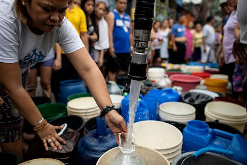 Residents of Addition Hills in Madaluyong City, Metro Manila, queue to recieve water distributed on water tank truck and fire trucks, on March 15, 2019.