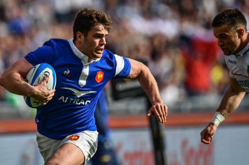 France's wing Damian Penaud runs on his way to score a try.