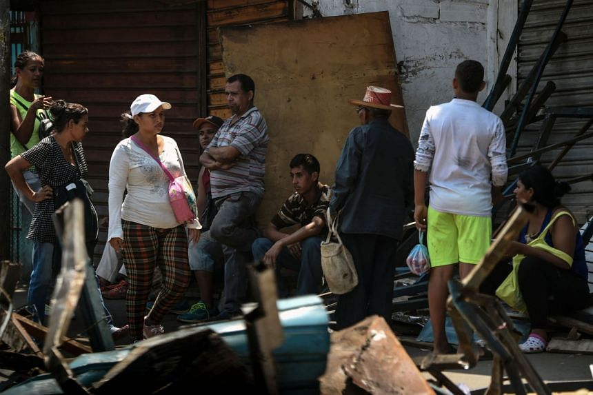 Locals sit on the street during a massive blackout that has paralysed Venezuela.