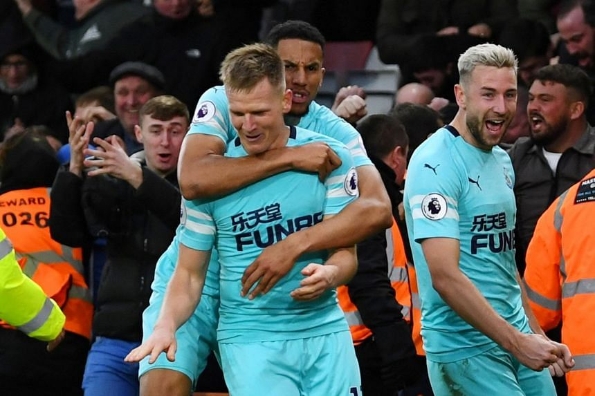 Ritchie celebrates scoring their second goal with Isaac Hayden and Paul Dummett.