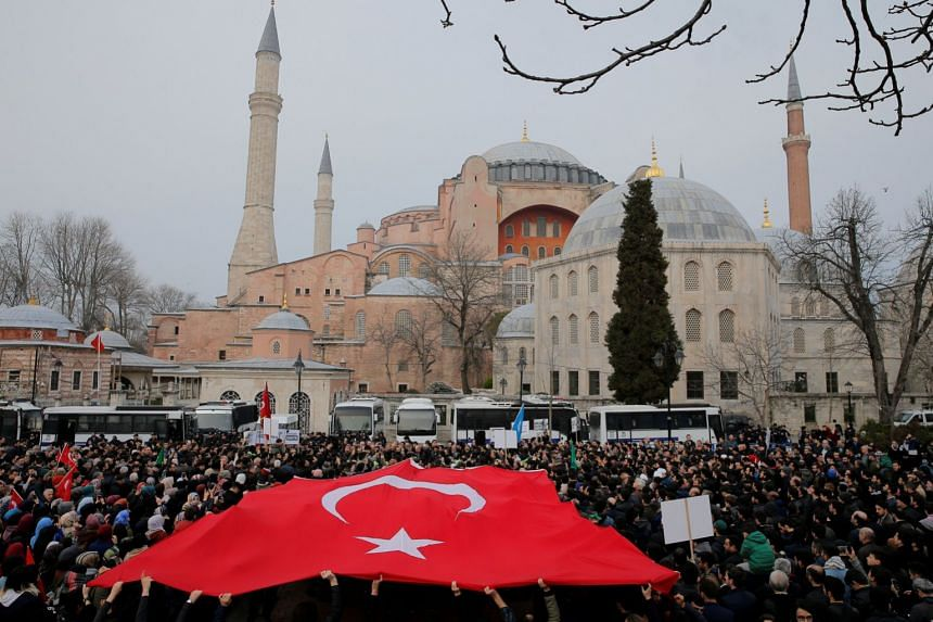 Demonstrators wave a Turkish flag during a protest against the New Zealand mosque attack in front of the Hagia Sophia in Istanbul.