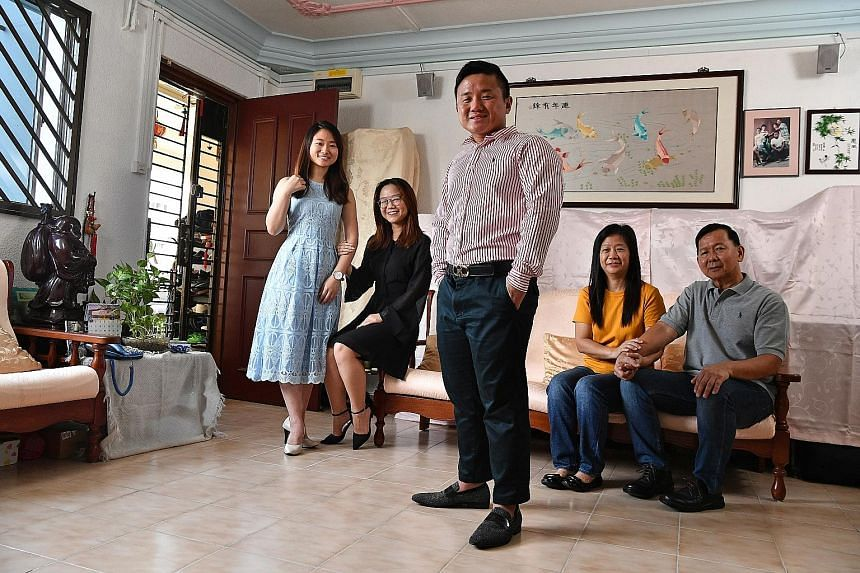 Mr Stewart Lim, 30, an associate group director at PropNex, in the living room of his four-room Housing Board flat in Bukit Panjang, where he lives with younger sisters Sabrina (left) 26, and Stella, 20, and parents Tay Bong Him, 56, and Lim Yew Teck, 58.
