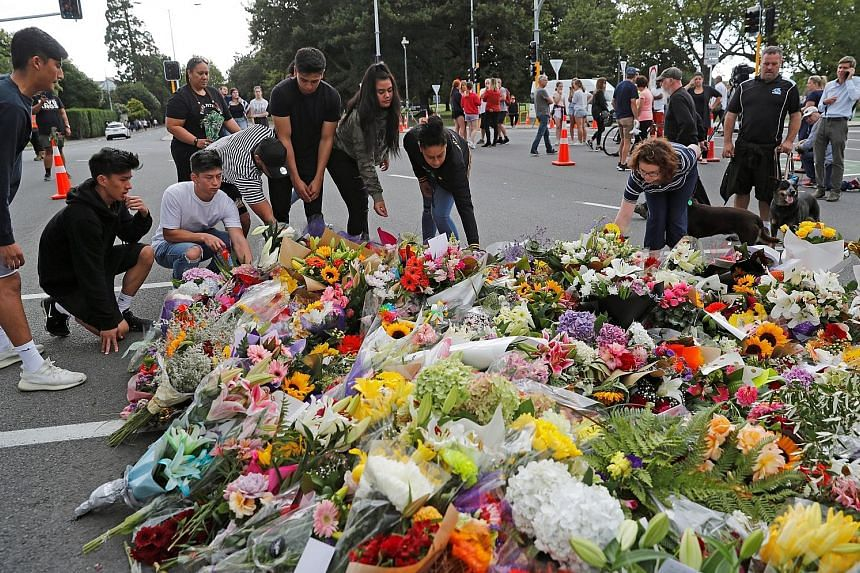People placing flowers yesterday at a memorial to the victims of Friday's mosque attacks, near a police line outside Al Noor Mosque in Christchurch, New Zealand. A total of 49 people died in the attacks and dozens were wounded.