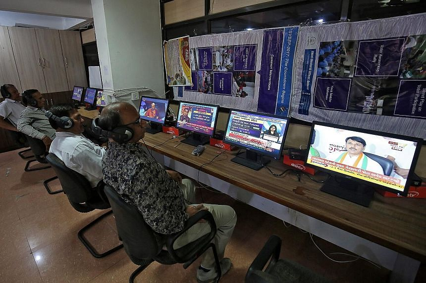 India will implement a paper audit trail for votes cast using the electronic voting machine (left). Election staff at a district collector's office in Ahmedabad last Thursday monitoring TV programmes to ensure the election code of conduct is being fo