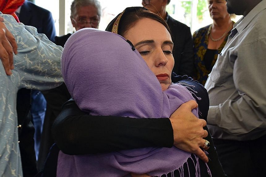 New Zealand Prime Minister Jacinda Ardern comforting a member of the Muslim community yesterday after the mass shooting in Christchurch.