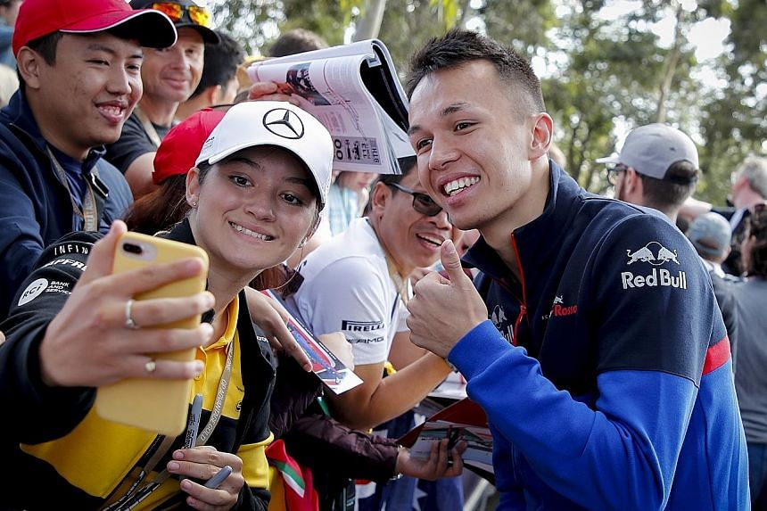 Thai F1 driver Alexander Albon of Scuderia Toro Rosso poses for a photo with a fan at the paddock ahead of the Australian Grand Prix at Albert Park in Melbourne.
