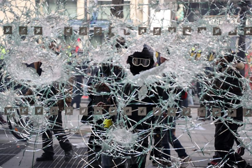 Riot police facing the protesters on the Place de l'Etoile in Paris during clashes yesterday. Police fired tear gas and water cannons at the protesters. A yellow vest protester is seen through a shop window he destroyed in the Champs Elysees. Demonst