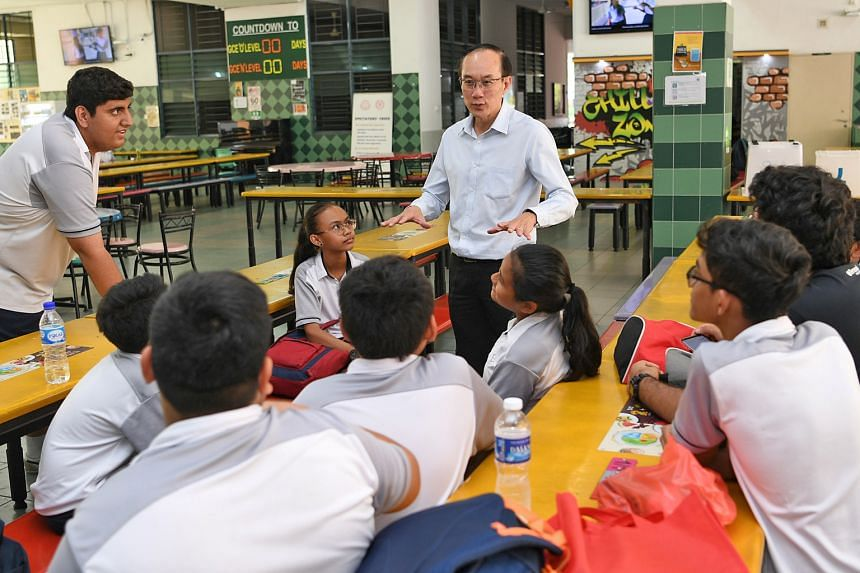 """Mr Tan Chor Pang, principal of Boon Lay Secondary School, with some of its students. During his 35 years as an educator, he has taught students from both the Normal and Express streams and has never minded teaching weaker children, saying: """"I felt li"""