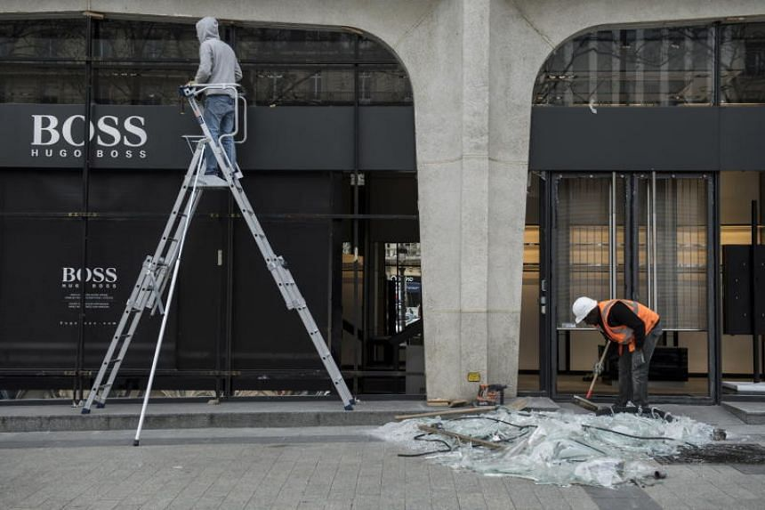 Workers cleaning up the front of a damaged store in the Champs Elysees after Yellow Vest protesters clashed with police, in Paris on March 17, 2019.