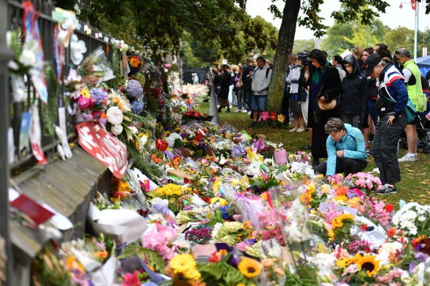 Members of the public placing flowers at a makeshift memorial for the victims of the mosque mass murders at the Botanical Gardens in Christchurch on March 17, 2019.