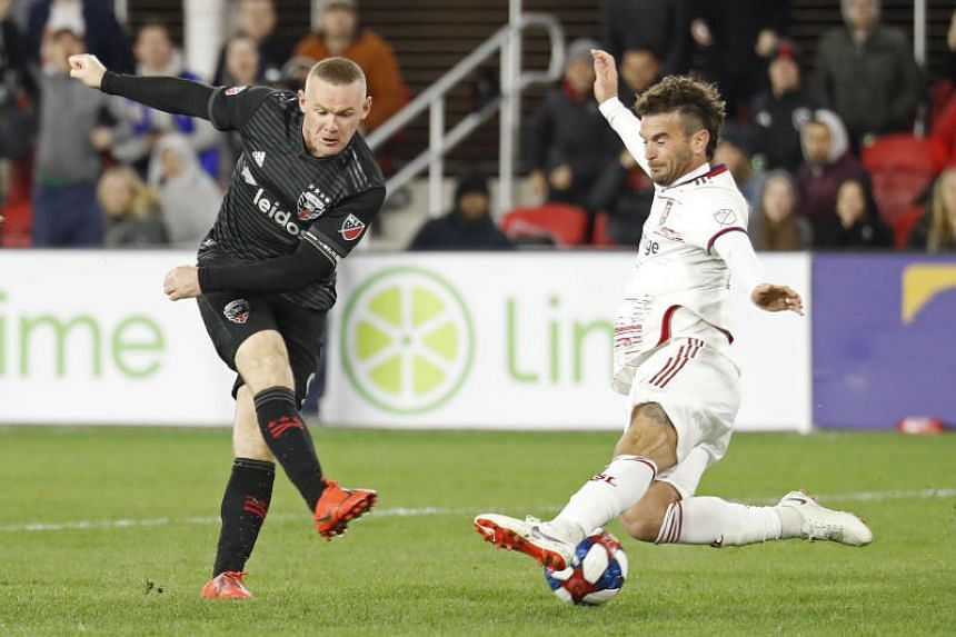 D.C. United forward Wayne Rooney (left) shooting the ball past Real Salt Lake midfielder Kyle Beckerman during their MLS match on March 16, 2019.