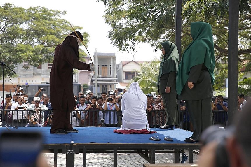 A woman being caned in public at the Lam Gugom Mosque in Banda Aceh in Indonesia's Aceh province earlier this month. Public floggings are well attended, with covered tents for dignitaries. Syariah enjoys popular support as it underscores the province