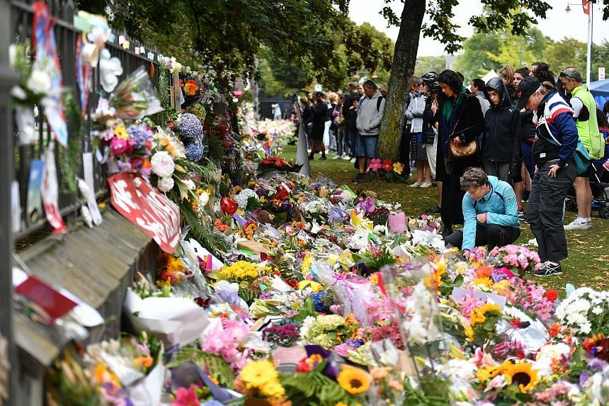 People placing flowers at a makeshift memorial for the massacre victims at the Christchurch Botanic Gardens yesterday.