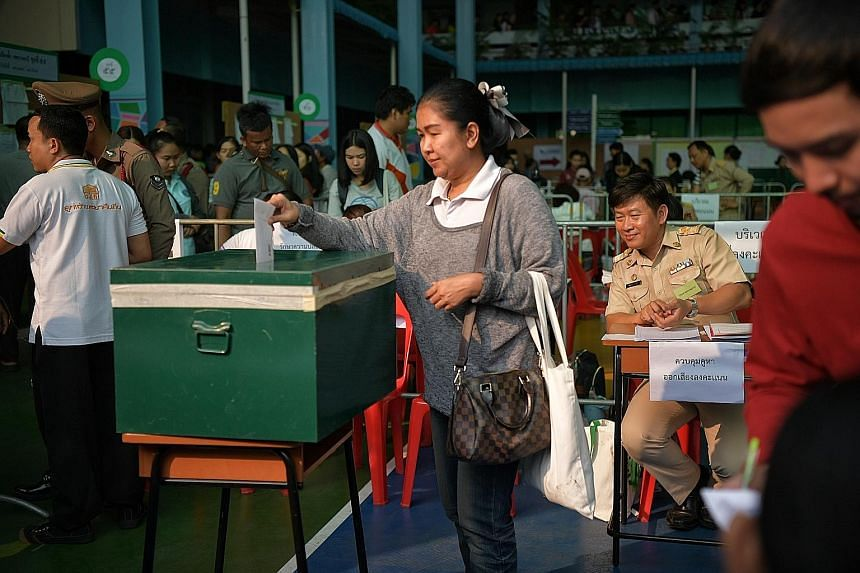 Thai voters queueing to cast their ballots during early voting at a polling station in Bangkok yesterday. In all, 80 parties are contesting 500 seats in the legislature, of which 350 are constituency seats and 150 are party-list seats. A woman castin