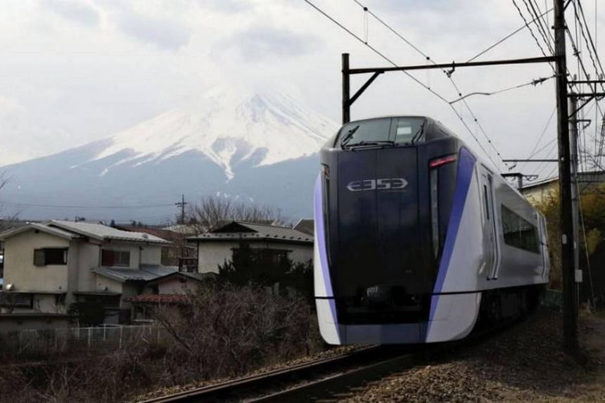 The Fuji Kaiyu limited express train in Fujiyoshida, Yamanashi Prefecture, with  Mount Fuji in the background.