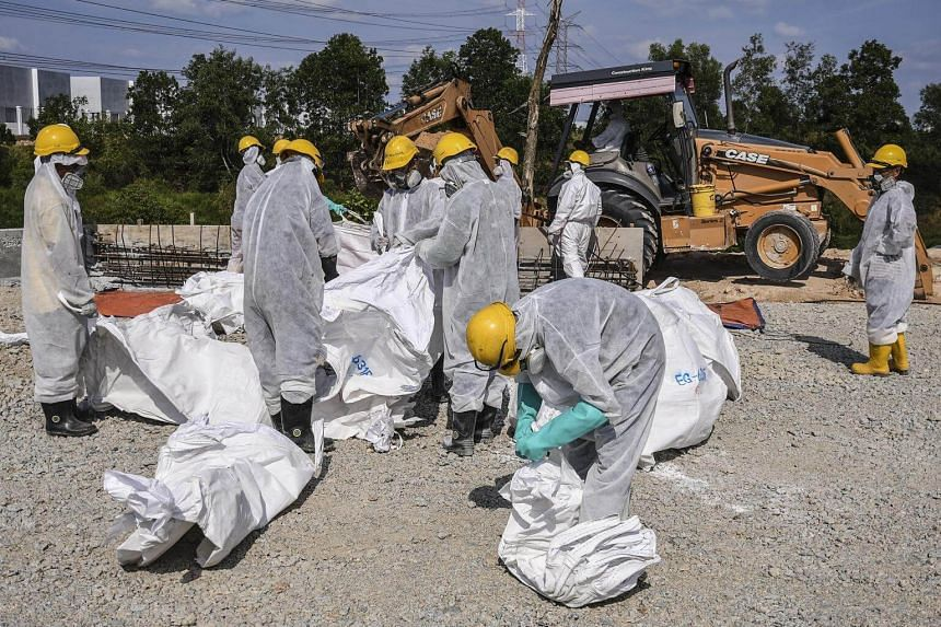 Emergency personnel wearing protective suits prepare to clean up the Sungai Kim Kim river in Pasir Gudang, on March 14, 2019.