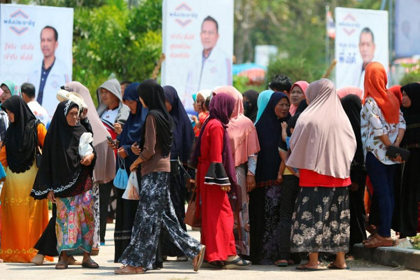People line up for their early vote for the upcoming Thai election at a polling station in Narathiwat province, Thailand, on March 17, 2018.