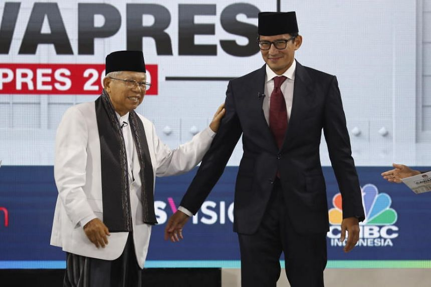 Indonesian President Joko Widodo's vice-presidential candidate Ma'ruf Amin (left) walks with rival Prabowo Subianto's running mate Sandiaga Uno during a debate among the No. 2 picks in Jakarta on March 17, 2019. Indonesia expects to hold its presiden
