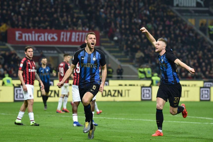 Inter Milan's Stefan de Vrij (left) celebrates after scoring a goal against AC Milan at the San Siro stadium, on March 17, 2019.