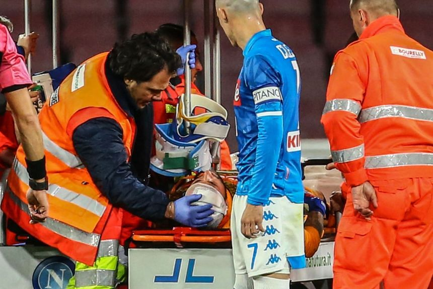 Napoli's Colombian goalkeeper David Ospina receiving treatment after sustaining a head injury during the Italian Serie A football match against Udinese.