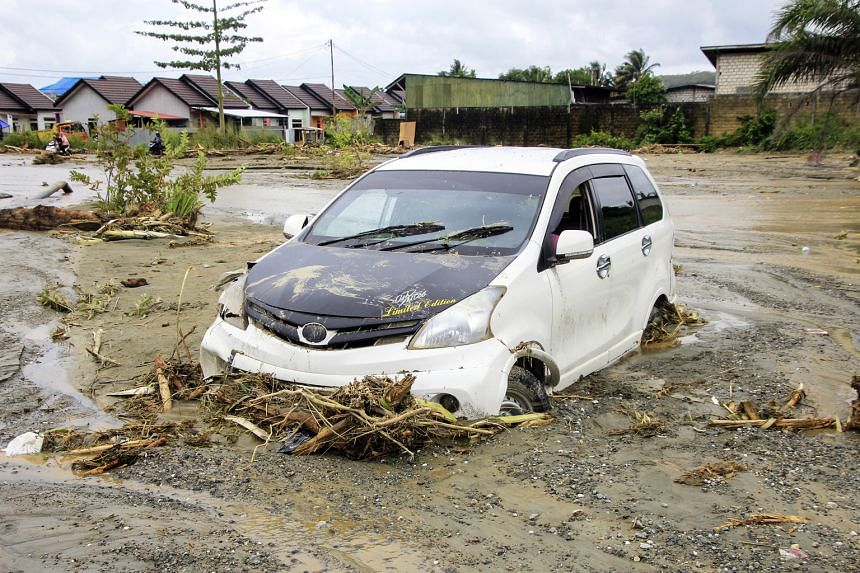 A car is stuck in the mud after getting washed away by flash floods in Sentani, in Indonesia's Papua province.