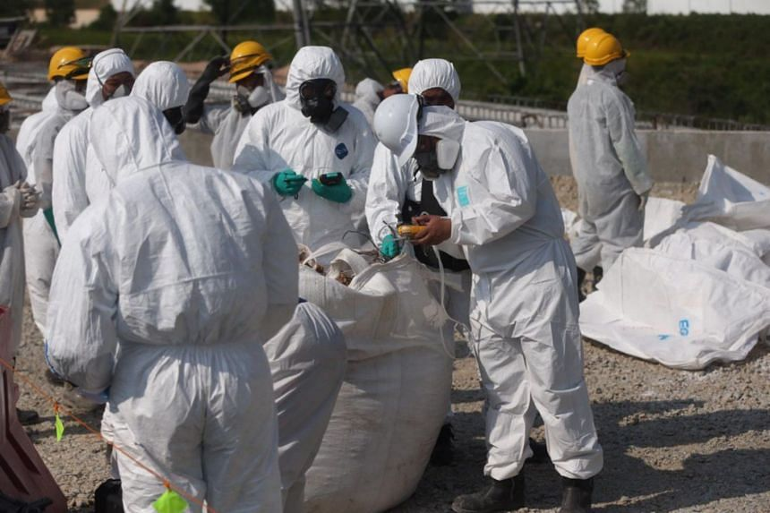 Personnel from the Emergency Medical Services and the military take soil samples along a site that is believed to have been the area where chemical waste was dumped in Pasir Gudang, Johor, on March 14, 2019.