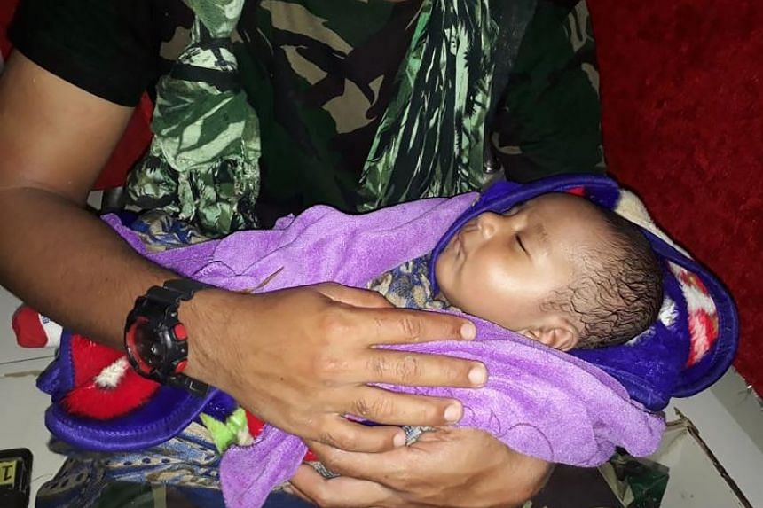 The five-month-old was plucked from debris inside a house where his mother and siblings were found dead in the hard-hit north-eastern town of Sentani, Indonesia.