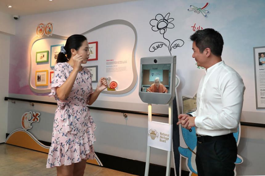 Mr Alvin Tan, assistant chief executive of the National Heritage Board, and Ms Lu Cai Xia, assistant curator of the Sun Yat Sen Nanyang Memorial Hall, interacting with the mobile Telepresence Robot.