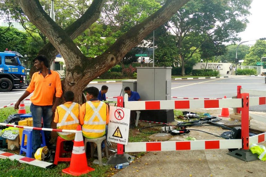 Workers at a site in Boon Lay Avenue where repair works were being carried out. A cut fibre-optic cable in Jurong West disrupted Internet and fixed voice services for almost 30 hours in April 2017, the longest such outage to date.
