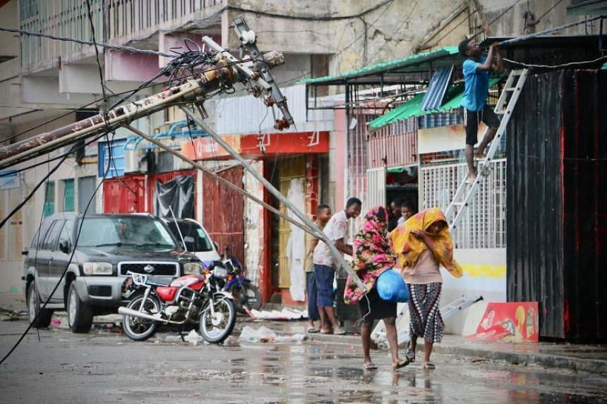 Residents are seen protecting themselves from the rain in the aftermath of the passage of Cyclone Idai in Beira, Mozambique, on March 17, 2019.