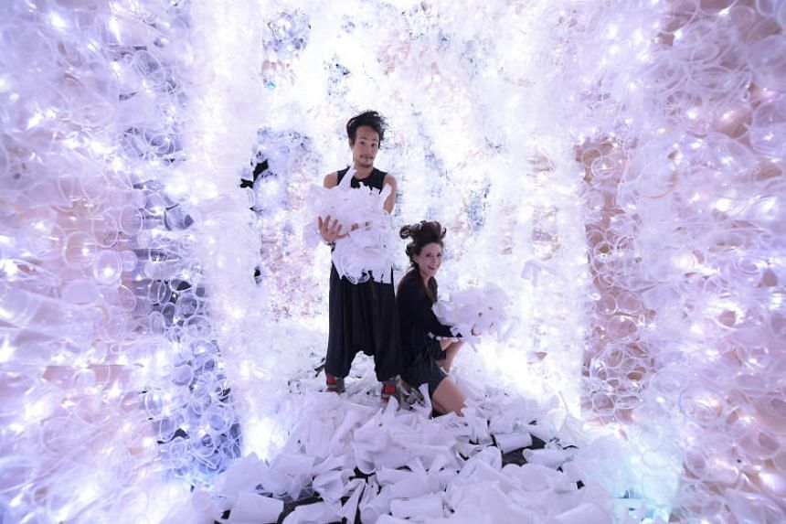 Artist Benjamin Von Wong and social impact strategist Laura Francois in their immersive sculpture at Marina Barrage. The installation, on display at Plastikophobia, is made from 18,000 used plastic cups collected from hawker centres.