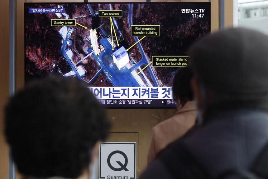 South Korean people watch a television broadcast at Seoul Station in Seoul on March 7, 2019. South Korea's spy agency said on March 5 that it detected signs of the North restoring part of the Sohae satellite launch facility near its border with China